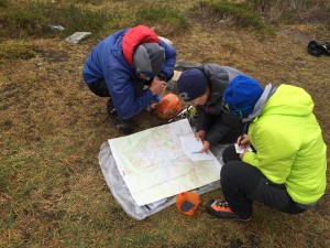 Exam candidates and examiner lokking over a map of the Eldorado Peak zone.  While everybody on AMGA exams these days tends to use some app for navigation, such as Gaia, a guide must be able to use an old fashioned paper map too.  Taking a bearing on a map and in the field as well as plotting a bearing on the map and in the field, are skills an AMGA Certified  Alpine Guide should know.