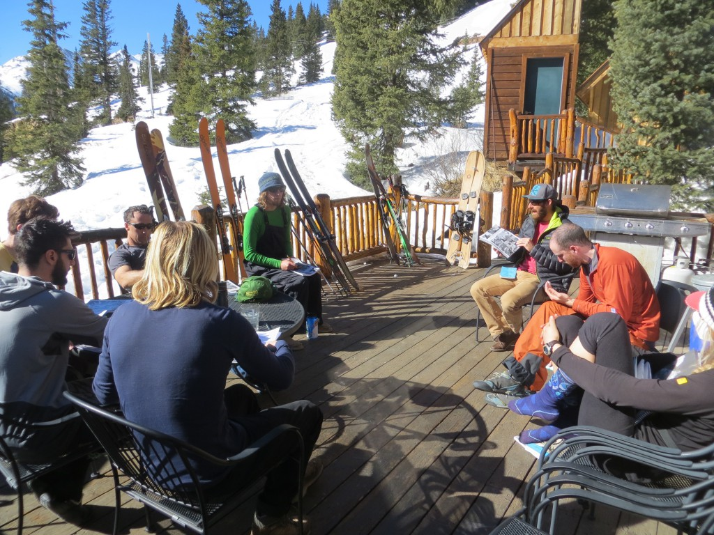 Students on an AIARE Level 2 having a classroom session on the deck of the Addie S Cabin on Red Mountain Pass. San Juan Mountains, CO