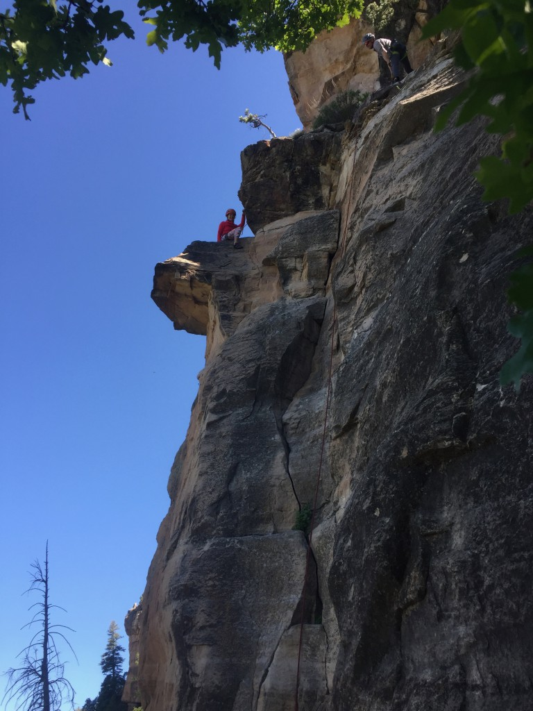 Topping out Dogs of Doom (5.8) at East Animas climbing area in Durango.